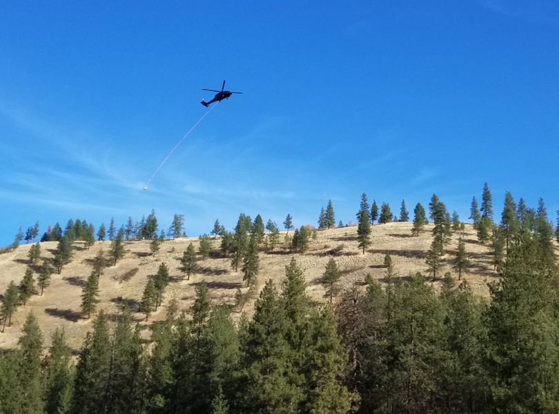 A helicopter hauls materials for an Avista transmission line project over the South Hill bluff on Oct. 23, 2017. (Rich Landers)
