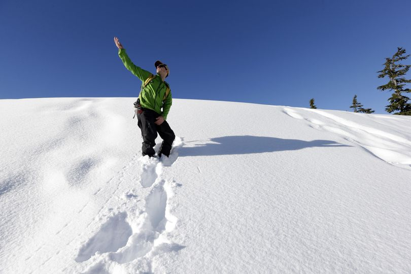 Eric Gullickson, an instructor with the Northwest Avalanche Center, points toward the sky as he explains how a slope heated by the sun can affect the possibility of an avalanche as he leads teenagers on an avalanche awareness field trip at Mount Baker, Washington. As more young adults head out of bounds to ski, snowboard or hike in the winter, experts are targeting their message about avalanche safety and knowledge to an even younger audience. (Elaine Thompson / Associated Press)