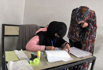 An Afghan election worker, left, registers a woman at the voter registration office in Kandahar province on Thursday.  (Associated Press / The Spokesman-Review)