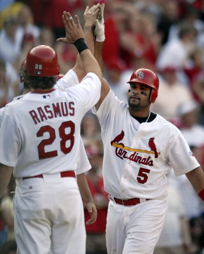 St. Louis' Albert Pujols receives congratulations after one of his two grand slams this season.  (Associated Press / The Spokesman-Review)