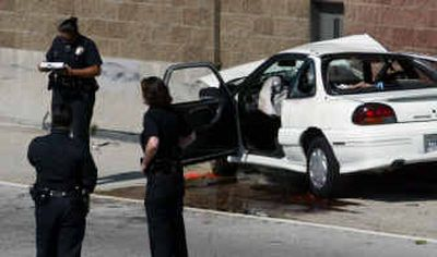 Los Angeles police investigate an accident on the 110 freeway, north of the 91 Freeway, April 13, in Los Angeles. The driver crashed into the freeway retaining wall after being shot, according to authorities.   (AP photo/Los Angeles Times, Bob Chamberlain / The Spokesman-Review)