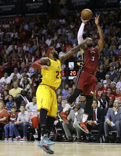 Heat's Dwyane Wade shoots over pal and ex-teammate LeBron James of Cavaliers. (Associated Press)