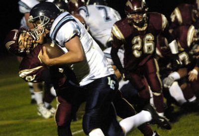 University's Joey Montes grabs the face mask of a Lake City player during Wednesday night's 29-9 non-league, season-opening loss to the visiting Timberwolves.   (Holly Pickett / The Spokesman-Review)