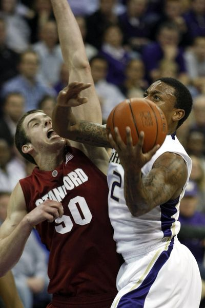 Huskies guard Isaiah Thomas drives to the basket against Jack Trotter of Stanford in the first half.  (Associated Press)