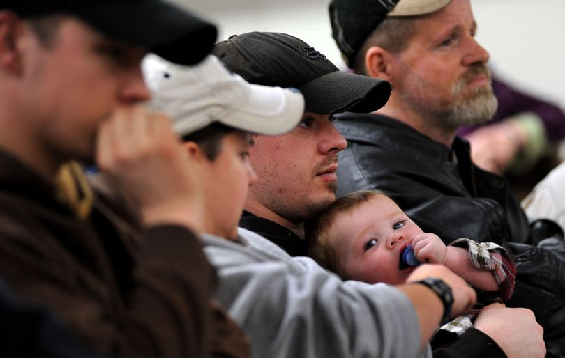 Lucky Friday miner, Brad Sala, of Mullan holds his 8 month-old-son Cael Sala during the press conference at Mullan City Hall on Saturday, April 17, 2011. One miner is still trapped in the mine after a cave in. (Kathy Plonka / The Spokesman-Review)