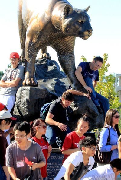 In this photo taken Aug. 17, 2011, freshmen climb down from the sculpture of the Washington State University mascot, Butch, during a walking-tour of the campus in Pullman, Wash., which is for all freshmen and transfer students. (Alan Berner / Associated Press)