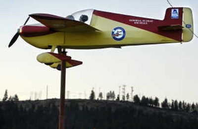 A 19-foot long plane on a flag pole serves as a windvane next to the main terminal at Felts Field. The windvane is a memorial to pilot Robert Heale.   (Holly Pickett / The Spokesman-Review)