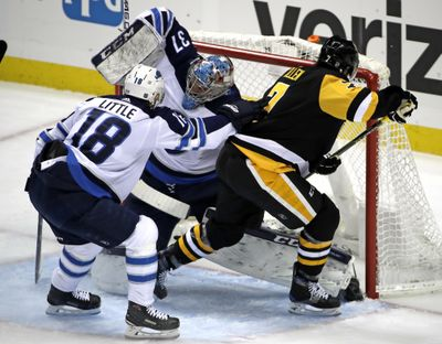 Pittsburgh Penguins' Matt Cullen (7) gets the puck past Winnipeg Jets goaltender Connor Hellebuyck (37) for a goal with Bryan Little (18) defending during Friday's game. Pittsburgh won 4-0. (Gene J. Puskar / Associated Press)