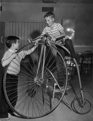 Randy (left) and Bruce Dill, sons of Mrs. Dorothy Dill, 1216 W. College, try out an Overman racing bicycle on display at the Cheney Cowles museum, 2316 W. First, Nov. 6, 1960. The bike, built in 1886 in New England and sold new for $135, was typical of the type used in the 1880s.     (Photo Review / The Spokesman Review)