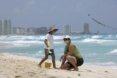 Wearing protective face masks as a precaution against swine flu contagion, Kevin Solis plays with his mother, Abdi Santoyo, at a nearly deserted beach in Cancun, Mexico, on Thursday.  (Associated Press / The Spokesman-Review)