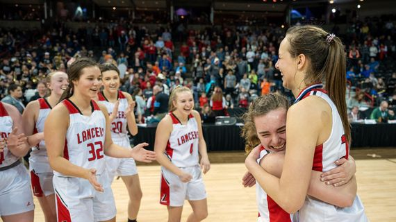 Liberty's Ava Budde, left, hugs fellow guard Maisie Burnham  after the Lancers defeated Northwest Christian 64-44 during a girls State 2B semifinal  in the Spokane Arena. (Colin Mulvany / The Spokesman-Review)