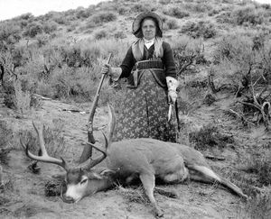 """A.G. Wallihan, photographer. Augusta Wallihan—Grocery Shopping. Albumen print, circa 1895. Standing over one of her many trophy mule deer, subsistence-and-sport huntress """"Gusty"""" Wallihan appears every inch the frontier matron with her dressy bonnet, prairie-pattern cartridge belt, floral-embroidered gauntlets, hunting knife, and Remington-Hepburn rifle.     (Museum of Northwest Colorado)"""