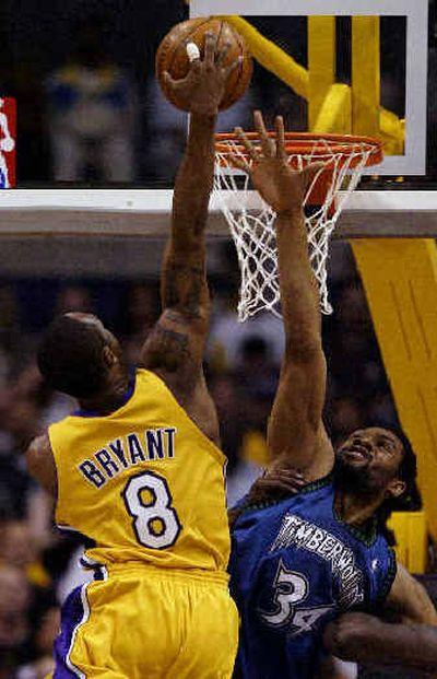 L.A.'s Kobe Bryant dunks over Michael Olowokandi of Minnesota. L.A.'s Kobe Bryant dunks over Michael Olowokandi of Minnesota.   (Associated PressAssociated Press / The Spokesman-Review)