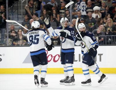 Winnipeg Jets' Mathieu Perreault, Jack Roslovic and Bryan Little, from left, celebrate after defenseman Tyler Myers's goal against the Vegas Golden Knights during the third period of Game 4 of the NHL Western Conference finals hockey playoff series Friday, May 18, 2018, in Las Vegas. (John Locher / Associated Press)
