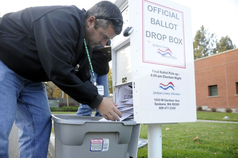Elections worker Mike McLaughlin removes ballots from the drop box outside the South Hill Library on Monday. For a list of drop boxes in Spokane County and resources for other counties, see Page A12. (The Spokesman-Review)