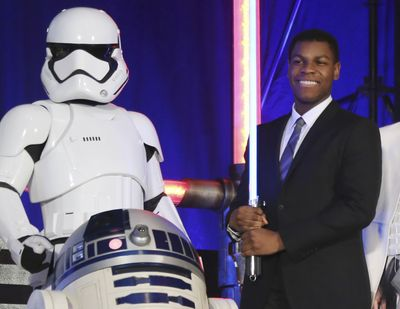 Actor John Boyega, right, poses with Star Wars characters during the Japan Premiere of their latest film