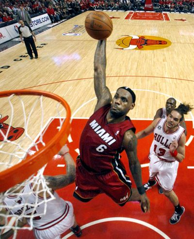 Miami's LeBron James dunks over Bulls forward Carlos Boozer with Joakim Noah looking on during Wednesday's Game 2. (Associated Press)