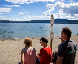 The Young family looks over City Beach and Lake Coeur d'Alene on Wednesday afternoon as people swim without the supervision of lifeguards. The city of Coeur d'Alene will not employ lifeguards to watch over the beach this summer. (Jake Parrish/Coeur d'Alene Press photo)