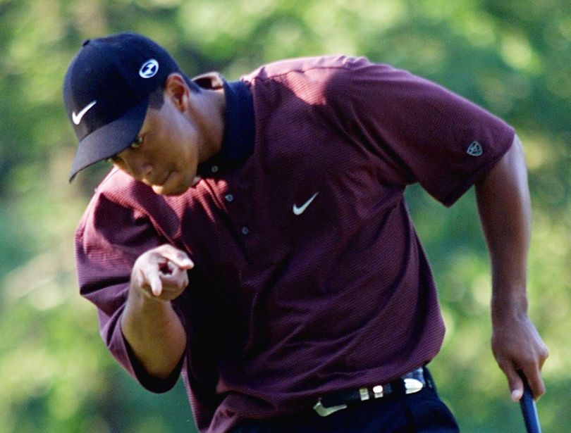 FILE - In this Aug. 20, 2000 file photo, Tiger Woods points to his ball as it drops for birdie on the first hole of a three-hole playoff against Bob May at the PGA Championship at the Valhalla Golf Club in Louisville, Ky. On his web site Friday night, Dec. 11, 2009, Woods announced that he is taking an indefinite break from professional golf. (Chuck Burton / Associated Press)