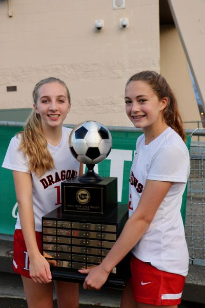 St. George's girls soccer players Abby Jones, left, and Maddy Christiansen hold the 2016 state championship trophy. (Bob Jones / Courtesy)