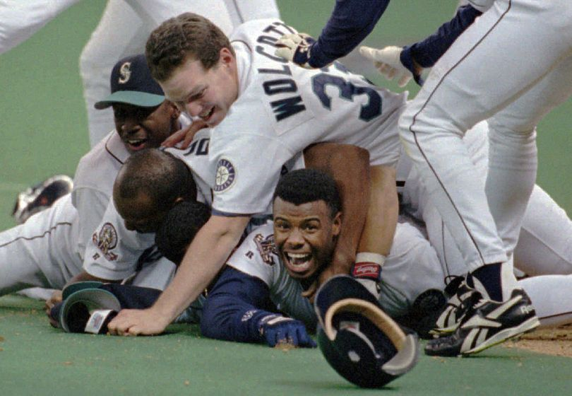 FILE - In this Oct. 8, 1995, file photo, Seattle Mariners' Ken Griffey Jr. smiles from beneath a pile of teammates who mobbed him after he scored the winning run in the bottom of the 11th inning of a baseball game against the New York Yankees in Seattle.  (Elaine Thompson / Associated Press)
