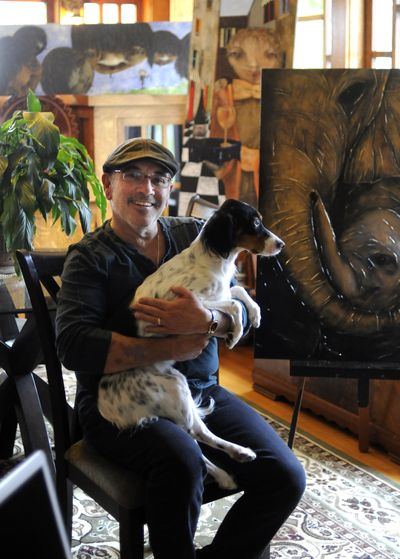 Tom Norton poses for a photo with his dog Sophie in his home on the South Hill on Wednesday. (Liz Kishimoto)