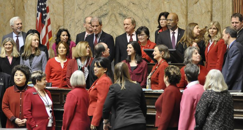 OLYMPIA – Supporters of changes to the Equal Pay Act, many of them dressed in red to mark International Women's Day, pose for a photo at the House Rostrum after the bill passed Wednesday. (Jim Camden / The Spokesman-Review)