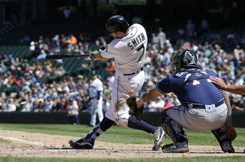 Seattle Mariners' Seth Smith hits a solo home run as San Diego Padres catcher Christian Bethancourt looks on in the fifth inning on Tuesday in Seattle. It was Smith's second home run of the game. (Ted S. Warren / Associated Press)