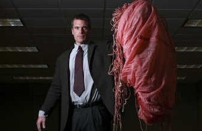At left, FBI agent Larry Carr displays a parachute, left behind by D.B. Cooper, at the FBI Seattle office Nov. 14. Below, a $20 plane ticket from Portland  to Reno, Nev., purchased by D.B. Cooper is part of the body of evidence gathered in the investigation of his hijacking. Seattle Post-Intelligencer  (Photos by Andy Rogers Seattle Post-Intelligencer / The Spokesman-Review)
