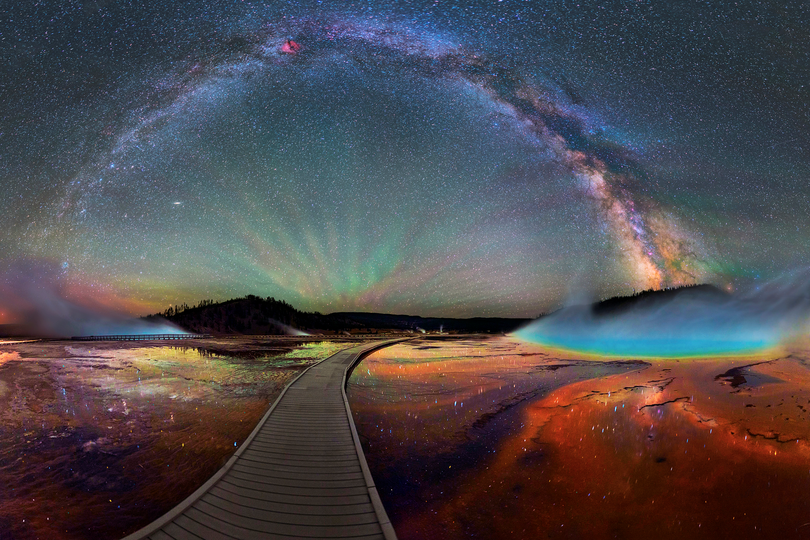 Midway Geyser Basin in Yellowstone National Park was never so enchanting as in this multi-image panorama shot created under the Milky Way on a boardwalk to Grand Prismatic Spring, the largest hot spring in the park. The image was shared with the national park service by photographer David Lane on Instagram  (David Lane)