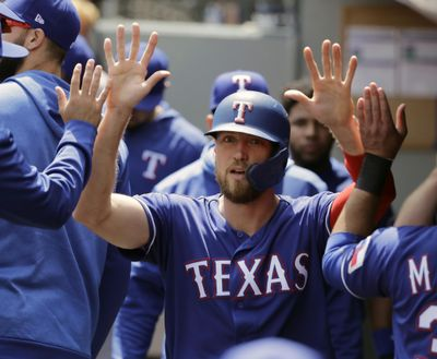 In this May 29, 2019 photo, Texas Rangers' Hunter Pence is greeted in the dugout after he scored on an RBI single hit by Asdrubal Cabrera during the first inning of a baseball game in Seattle. Pence was being wished well in retirement last year. Next week, he'll be at the All-Star Game representing the Rangers. (Ted S. Warren / Associated Press)