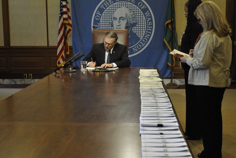 OLYMPIA -- Gov. Jay Inslee begins signing more than four dozen bills Thursday morning in his office conference room. (Jim Camden)