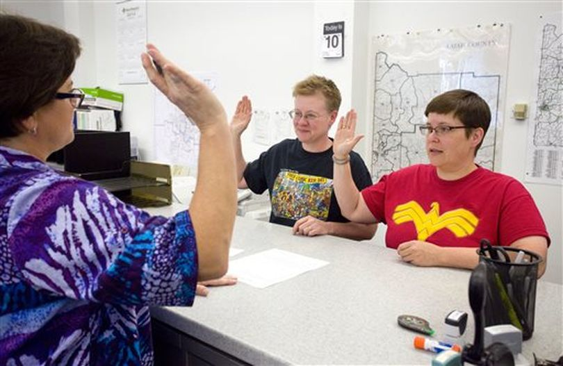 Katherine Sprague, center, and Tabitha Simmons, right, take an oath under the direction of Deputy Recorder Stacey Chapman while applying for their marriage license at the Latah County Courthouse in Moscow, Idaho, on Friday, Oct. 10, 2014. Sprague and Simmons were the first couple to be issued a same-sex marriage license in Latah County. (AP/Moscow-Pullman Daily News / Geoff Crimmins)