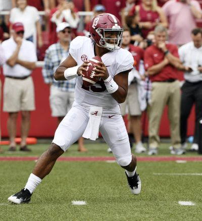 In this Oct. 6, 2018 photo, Alabama quarterback Tua Tagovailoa rolls out before throwing a touchdown pass on the first play of the game against Arkansas in the first half of an NCAA college football game, in Fayetteville, Ark. Tagovailoa is the offensive player of the year and one of five members of the top-ranked Crimson Tide to earn first-team honors on The Associated Press All-Southeastern Conference team, announced Monday, Dec. 3, 2018. Tagovailoa, one of the prime contenders for the Heisman Trophy, has thrown 37 touchdown passes with only four interceptions to rank second nationally in passing efficiency. (Michael Woods / Associated Press)