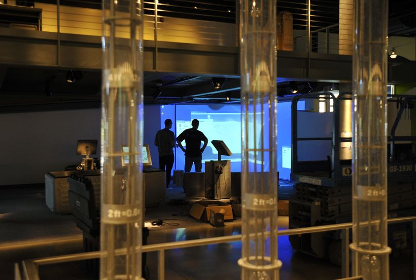 Christian Bannister and Shawn Sessions work on the installation of an exhibit at the new Mobius Science Center in downtown Spokane. (Dan Pelle)