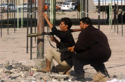 Armed men of the militia of radical Shiite cleric Muqtada al-Sadr take positions Sunday in central Basra, Iraq, demanding the release of one of their commanders, Sheikh Ahmed Fartosi.   (Associated Press / The Spokesman-Review)