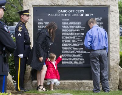 Lindy Moore, the wife of fallen Coeur d'Alene policeman Gregory K. Moore, helps remove a black ribbon revealing his name with daughter Gemma, 2 and son Dylon Moore, 13, on the Idaho Peace Officers' Memorial Thursday Meridian, Idaho. (Darin Oswald / Associated Press)