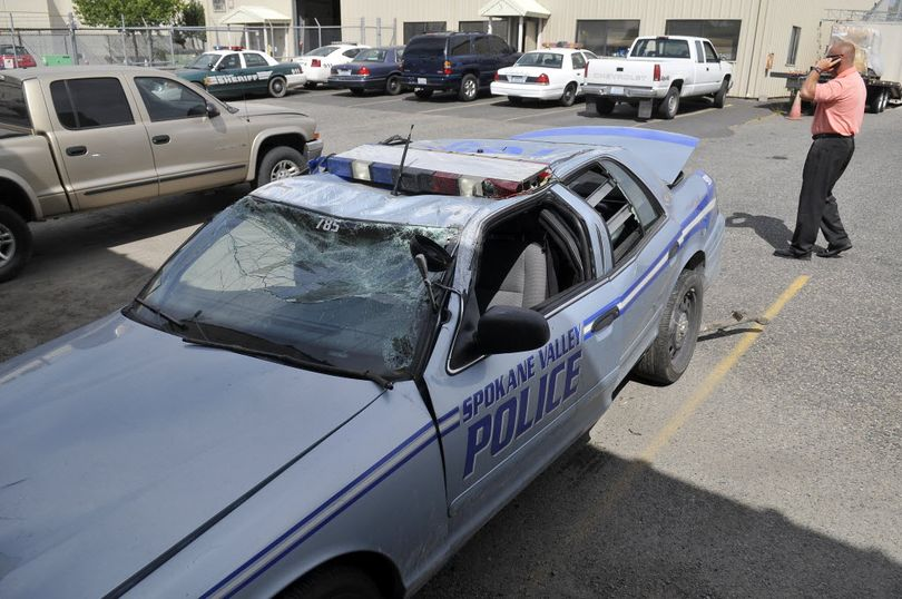 A Spokane Sheriff's car, driven by Deputy Rustin Olson in a crash last Friday, sits in the Sheriff's parking lot Wednesday, Aug. 8, 2012. The car left the roadway and flipped on South Pines Rd. after hitting a chunk of firewood placed or dropped in the roadway. Olson was speeding to a call about a fight at South Pines Elementary when it happened, but there was no fight found, leading police to suspect a hoax designed to catch a police officer driving by and cause an accident. (Jesse Tinsley / The Spokesman-Review)