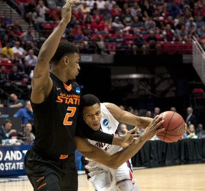 Gonzaga's Angel Nunez is hacked by against Oklahoma State's Le'Bryan Nash in the second half, March 21, 2014 at the NCAA Division I Men's Basketball Championship second round game in San Diego.  (Dan Pelle)
