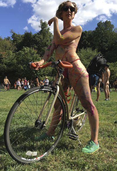 In this Sept. 9, 2017 photo, Olivia Neely, a topless cyclist wearing body paint, motions before the start of that year's annual Philly Naked Bike Ride in Philadelphia. Organizers of the Philly Naked Bike Ride say this year's event will take place Aug. 28, 2021, after last year's event was cancelled due to COVID-19, but masks will be required, even if pants and shirts are not.  (Dino Hazell)