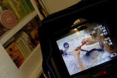 A monitor shows Sondra Barrington making a scarf and pin for HGTV.  (Brian Plonka / The Spokesman-Review)