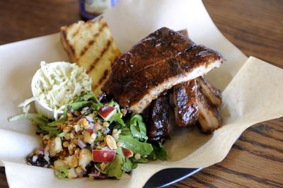 This platter from Lazy Bones Barbecue holds a pound of barbecue ribs, an apple-lentil salad, a scoop of vinegar coleslaw and a slab of grilled bread. (Jesse Tinsley / The Spokesman-Review)