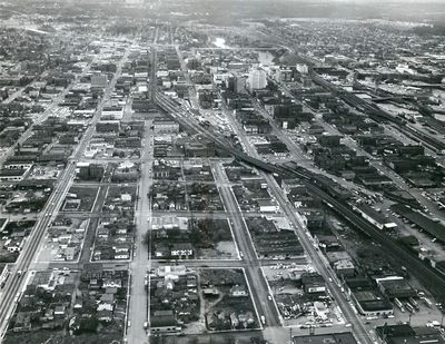 Early 1960s - In this aerial photo looking west over downtown Spokane, Washington, the Northern Pacific tracks winds from lower right, past the NP depot at 1st Ave. and Bernard St., and west down Railroad Ave. The NP line, connected in 1883, was the first transcontinental railroad through Spokane. As Interstate 90 was finished and Expo 74 construction was underway, the railroad companies agreed to put all rail traffic on the original NP corridor. (SPOKESMAN-REVIEW PHOTO ARCHIVE / SR)