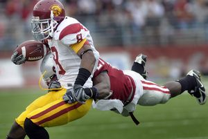 Washington State's Chima Nwachukwu takes to the air in an attempt to stop USC running back Ronald Johnson during the first half.  (Christopher Anderson / The Spokesman-Review)