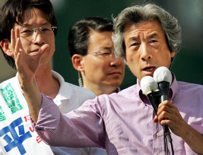 Japan's Prime Minister Junichiro Koizumi, right, speaks to the crowd as his party candidate Masaaki Taira, left, listens, during a campaign stop for his ruling Liberal Democratic Party in Tokyo Saturday.   (Associated Press / The Spokesman-Review)