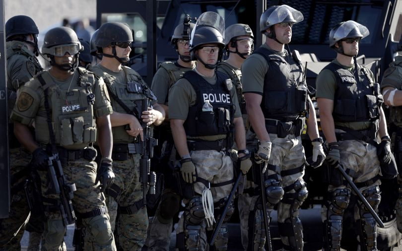 Police in riot gear watch protesters in Ferguson, Mo., on Wednesday. (Associated Press)
