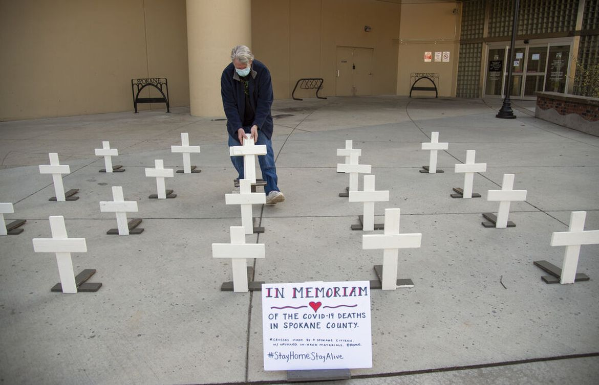 Tom Robinson, who crafted these wooden crosses, picks up the mobile display Monday, May 4, outside Spokane City Hall where he had set them up, with another member of a Facebook group Stronger Together Spokane to illustrate the Spokane death toll of COVID-19. The country surpassed 200,000 deaths from the virus this week. (JESSE TINSLEY)