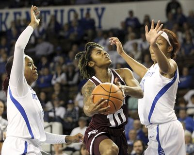 Mississippi State's Jazzmun Holmes, center, shoots between Kentucky's KeKe McKinney, left, and Nyah Tate, right, during the first quarter. (James Crisp / Associated Press)