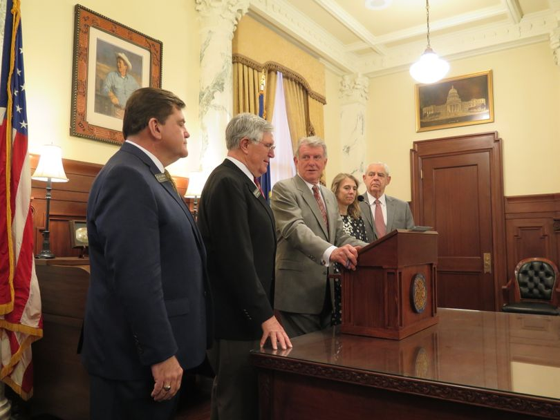 Gov. Butch Otter congratulates Rep. Lance Clow, second from left, at a ceremonial signing of HB 578, Clow's internet sales tax bill, on Friday morning, March 22, 2018. (The Spokesman-Review / Betsy Z. Russell)