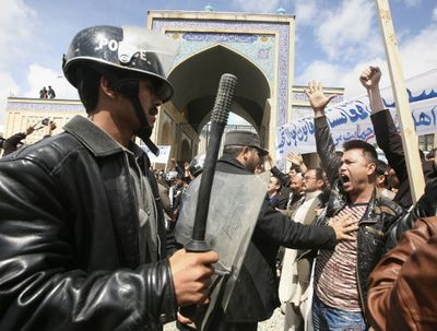 An Afghan police officer pushes a counterprotester during a demonstration in Kabul, Afghanistan, on Wednesday by women protesting a controversial new marriage law.  (Associated Press / The Spokesman-Review)